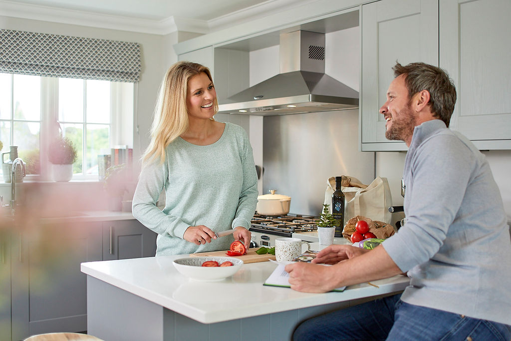 Lady chatting happily with a man in their kitchen