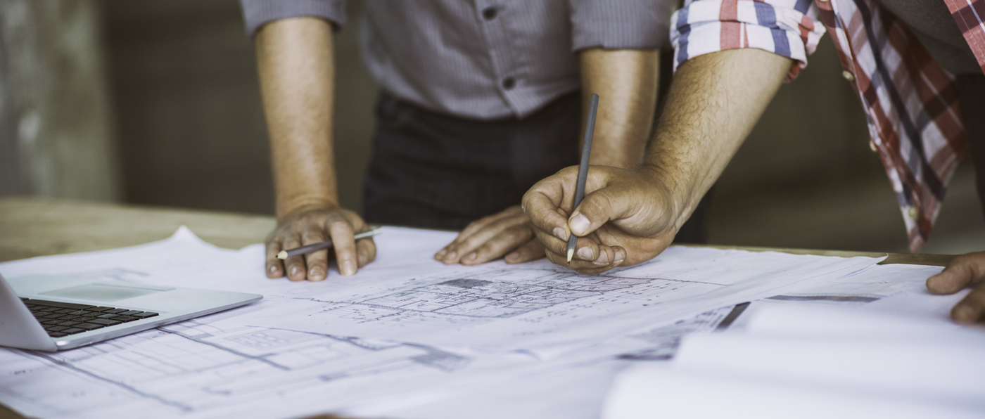 Close up of two architect's hands holding pencils over some building blueprints.