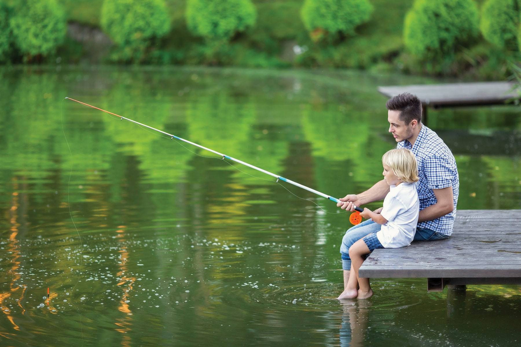 Father And Son Fising On A Lake